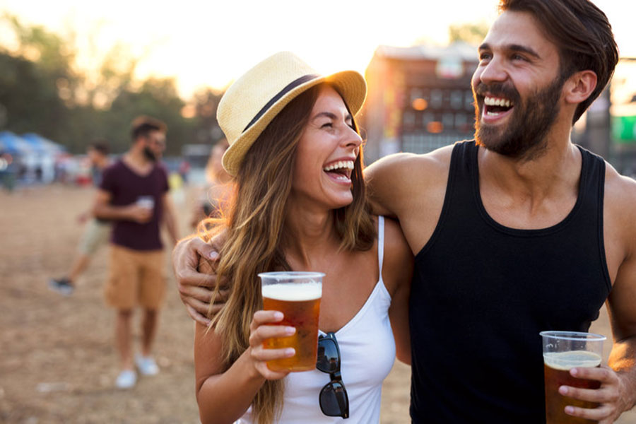 man and woman laughing while each holding a beer