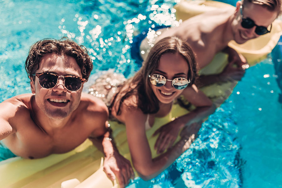 group of 3 people enjoying a sunny day in the pool
