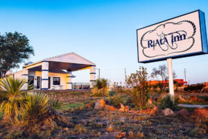 exterior building and road sign of Riata Inn Marfa
