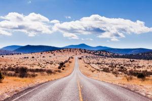 Straight road to horizon in high desert landscape